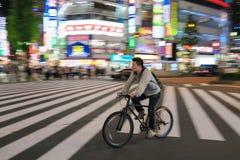 Scena di notte di Tokyo con il ciclista ad un passaggio pedonale in Shinjuku Fotografia Stock Libera da Diritti