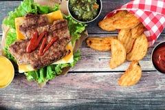 Scena di picnic di giorno del Canada con l'hamburger della foglia di acero sopra legno scuro Fotografia Stock