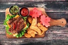 Scena di picnic di giorno del Canada con l'hamburger della foglia di acero sul bordo di pagaia Immagini Stock Libere da Diritti