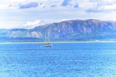Scena di Serene Scandinavian Fjord Village con la barca a vela Immagine Stock