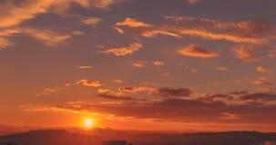 Scena di tramonto con la caduta del sole dietro le nuvole e le montagne nel fondo, colpo di lasso di tempo, cielo variopinto cald video d archivio