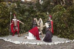 Scena di vita di Gesù L'uomo non identificato che ritrae Jesus Christ porta il grande incrocio di legno durante la rievocazione d Fotografie Stock Libere da Diritti