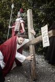 Scena di vita di Gesù L'uomo non identificato che ritrae Jesus Christ porta il grande incrocio di legno durante la rievocazione d Fotografia Stock Libera da Diritti