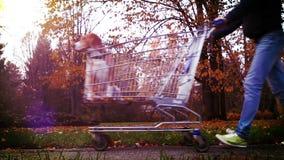Scena divertente: l'uomo porta il suo cane di animale domestico in un carrello del supermercato stock footage