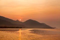 Scena drammatica di alba con, del mare, della montagna, del sole arancio e della barca Fotografia Stock Libera da Diritti
