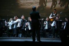 In scena, i musicisti e le soliste dell'orchestra dei fisarmonicisti (orchestra armonica) sotto la bacchetta del conduttore Fotografia Stock Libera da Diritti
