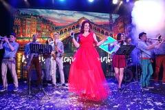 In scena, la menta verde del gruppo della schiocco-roccia dei musicisti ed il cantante Anna Malysheva Canto intestato rosso di Ja Fotografia Stock Libera da Diritti