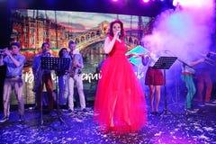 In scena, la menta verde del gruppo della schiocco-roccia dei musicisti ed il cantante Anna Malysheva Canto intestato rosso di Ja Fotografie Stock Libere da Diritti