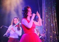 In scena, la menta verde del gruppo della schiocco-roccia dei musicisti ed il cantante Anna Malysheva Canto intestato rosso di Ja Immagine Stock Libera da Diritti