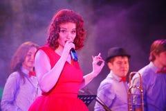 In scena, la menta verde del gruppo della schiocco-roccia dei musicisti ed il cantante Anna Malysheva Canto intestato rosso di Ja Immagini Stock Libere da Diritti