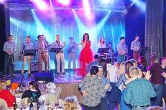 In scena, la menta verde del gruppo della schiocco-roccia dei musicisti ed il cantante Anna Malysheva Canto intestato rosso di Ja Immagine Stock