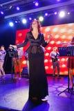 In scena, la menta verde del gruppo della schiocco-roccia dei musicisti ed il cantante Anna Malysheva Canto intestato rosso di Ja Fotografie Stock