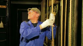 Scena pracownik w rękawiczkach obniża kabel podnośny mechanizm teatr zasłona i przymocowywa je zbiory