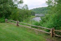 Scena rurale della natura di legno del recinto del paesaggio del fiume dell'erba verde Immagini Stock Libere da Diritti