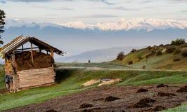 Scena rurale ed alta montagna nevosa su un fondo Fotografia Stock