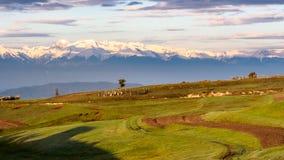 Scena rurale ed alta montagna nevosa su un fondo Fotografie Stock