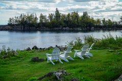 Scena tranquilla con le sedie di prato inglese di legno bianche su erba verde che trascura il lago Superiore nel Minnesota del No immagini stock libere da diritti