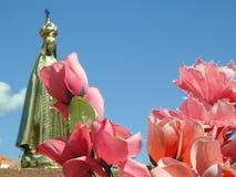 Scena in un cimitero: nella priorità alta, alcuni fiori rosa artificiali Nei precedenti, una statua dorata vaga della nostra sign immagine stock
