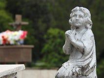 Scena in un cimitero: statua di un pregare della ragazza immagine stock libera da diritti