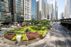 Scena urbana con il parco della città fra le alte strutture di vetro ed il calcestruzzo Fotografia Stock