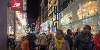 Scena urbana con la gente della folla alla strada dei negozi alla notte dentro Immagini Stock
