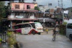 Scena vaga della via attraverso le finestre di automobile con goccia di pioggia nel Nepal Fotografie Stock Libere da Diritti