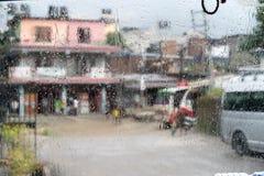 Scena vaga della via attraverso le finestre di automobile con goccia di pioggia nel Nepal Immagine Stock