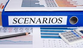 Scenarios binder on desk in the office. Scenarios - blue binder with text on desk in the office with pencil and calculator stock image