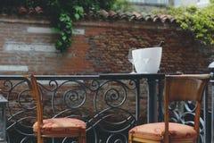 Scenary romántico, tabla con dos sillas, dos vidrios de vino y una botella de vino Foto de archivo