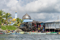Scene of activities at fishing port near mosque in Sabah, Malaysia. Royalty Free Stock Photography