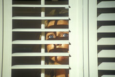Scene with actress looking through blinds Royalty Free Stock Photos