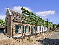 Scene with ancient cottage houses against a blue sky with clouds, Tilburg, Netherlands Royalty Free Stock Image