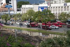 View across old city moat to busy street with many red mini vans or tuk tuk`s stock photos