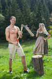 Scene of a Bavarian couple in traditional costumes chopping wood Royalty Free Stock Photos