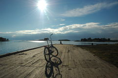 Scene with the bike. Calm summer day. Northern White sea at Solovetskiy island. View to the wooden embankment and the old russian bike on it Royalty Free Stock Image
