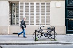 Scene of blurred man in leather jacket and jeans walking along street in Paris next to a locked bike. Scene of man in leather jacket and jeans walking along stock photo