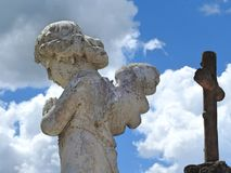 Scene in a cemetery: close-up of an old stone statue of a little angel with wings praying. royalty free stock photography