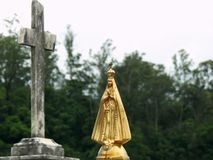 Scene in a cemetery: golden statue of Our Lady of Aparecida next to an unfocused stone religious cross. royalty free stock photo