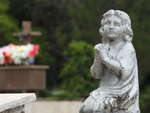Scene in a cemetery: statue of a girl praying. royalty free stock image