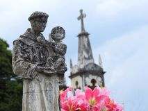 Scene in a cemetery: stone statue of a saint carrying the baby Jesus. royalty free stock photos