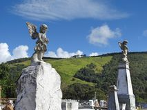 Scene in a cemetery: two old stone statues of angels on pedestals. royalty free stock photo