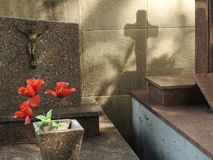 Scene in a graveyard: a vase with red fake flowers, a crucifix on a tombstone and the shadow of a cross on a wall. stock photo