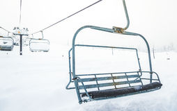 Scene of close up ski lift with seats going over the snow mounta Stock Images