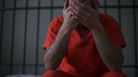 Scene of a depressed inmate in prison. Scene inside of a jail or prison