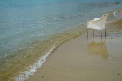 Scene of empty chair in white rattan sitting on sand beach with curved soft wave in shade of blue and clear sea water background. Ornos beach, Mykonos, Greece Royalty Free Stock Photos
