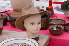 Scene from Flea market where people sell and buy used toys, clothes, pictures, kitchen ware and other vintage things. Scene from Flea market with model an hat Stock Photography