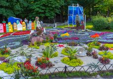 Scene on a flowerbed of a mermaid with a guy on a ship in a botanical garden, places to visit tourists stock photography
