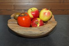 Scene of fruits in a wooden bowl on dark table stock photography