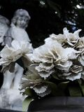 Scene in a graveyard: a vase with some white artificial flowers. In the blurred background, an old stone statue of an angel. Scene in a graveyard: in the stock photo
