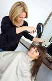 Scene in hair salon. Stylist drying woman hair in salon Royalty Free Stock Photos